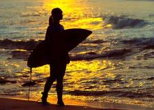 冲浪冲浪者的女孩看海洋海滩日落 剪影w 免版税图库摄影