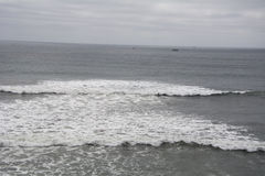 冲浪在一阴暗天在海滩 免版税库存照片