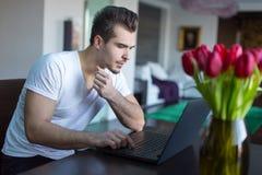 冲浪在互联网上的年轻人由膝上型计算机户内 免版税库存照片