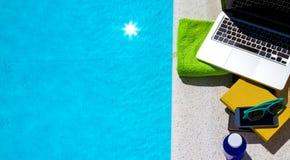 冲浪在互联网在游泳池附近 免版税库存图片