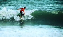 冲浪在有橙色潜水衣的海的冲浪者 库存图片