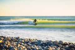 冲浪在海浪在日落或日出 冲浪在保温潜水服的冬天 免版税库存照片