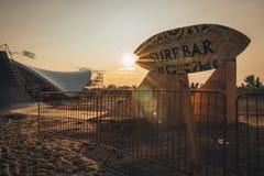 冲浪在海滩的酒吧标志在日落 免版税库存图片