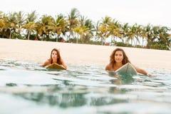冲浪在海洋的两个美丽的运动的女孩 免版税库存图片