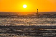 冲浪在海滩的日落的Kitesurfer在开普敦 免版税库存图片
