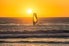 冲浪在海滩的日落的Kitesurfer在开普敦 库存图片