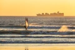 冲浪在海滩的日落的Kitesurfer在开普敦 免版税图库摄影