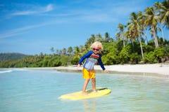 冲浪在热带海滩的孩子 冲浪者在海洋 免版税库存照片
