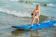 冲浪在热带海滩的小男孩 水橇板的孩子在海浪 孩子的活跃水上运动 孩子游泳与 库存图片