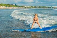 冲浪在热带海滩的小男孩 水橇板的孩子在海浪 孩子的活跃水上运动 孩子游泳与 库存照片