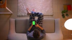 冲浪在电话的年轻男性博客作者特写镜头顶面射击社会媒介有绿色屏幕的,当坐长沙发时 股票视频