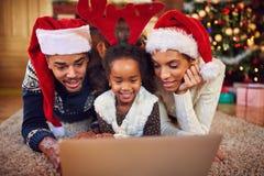 冲浪在计算机上的圣诞节购物的网上家庭 免版税库存图片