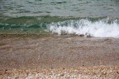 冲浪在贝加尔湖岸,清楚的绿色-紫色水 免版税库存照片