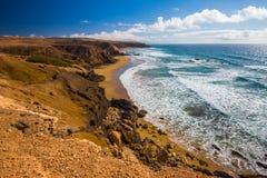 冲浪在La的青年人削去了与vulcanic山的海滩在费埃特文图拉岛海岛,加那利群岛,西班牙上的背景中 图库摄影