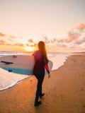 冲浪有冲浪板的女孩在日落和海洋在加拿大 免版税库存照片
