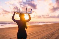 冲浪有冲浪板的女孩在海滩在日落或日出 冲浪者和海洋 库存图片