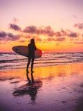 冲浪有冲浪板的女孩有温暖的日落或日出颜色的 图库摄影