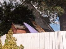 冲浪板冠上休息反对在墙壁后的一个棚子在庭院里 免版税库存照片