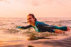 冲浪板游泳的可爱的冲浪者妇女在海洋 日落冲浪 免版税图库摄影
