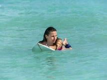 冲浪板的可爱的女孩在海洋 免版税库存照片