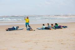 冲浪的教练在开阔水域附近指示海滩的新手冲浪者 库存照片