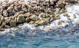 冲浪碰撞入在防波堤的岩石 免版税库存照片