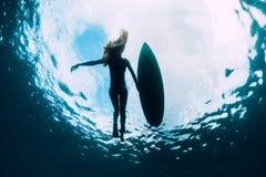 冲浪者与冲浪板的女子游泳 海浪女孩在海洋 免版税图库摄影