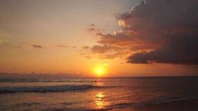 冲浪者乘坐在印度洋的橙色日落 股票视频