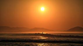 冲浪者冲浪在Chacahua国家公园的美丽的海岸的日出的,瓦哈卡,墨西哥 库存照片