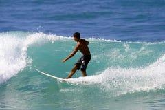 冲浪者冲浪的年轻人 免版税库存图片