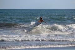 冲浪者在回声海滩Canggu巴厘岛印度尼西亚的骑马波浪 库存照片