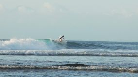 冲浪者在慢动作的巴厘岛印度尼西亚乘蓝色海浪 股票录像