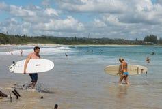 冲浪者在拜伦海湾海滩走  库存照片