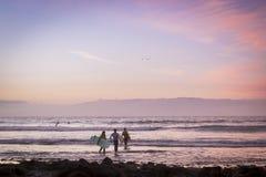 冲浪者在波浪,在海岸的明亮的日落,特内里费岛冲浪, 免版税库存图片