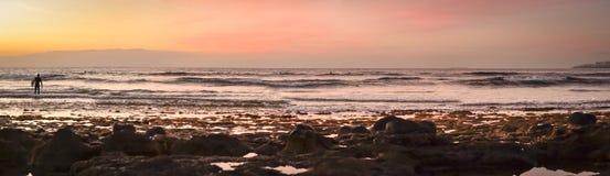 冲浪者在波浪,在海岸的明亮的日落,特内里费岛冲浪, 库存图片