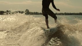 冲浪者在wakeboard的骑马波浪在慢动作 冲浪在日落的人 股票视频