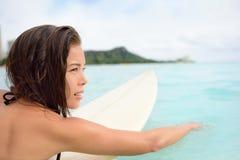 冲浪者女孩冲浪的paddeling在冲浪板 免版税库存图片