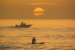 冲浪,与日出的划船 免版税库存图片