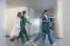 冲通过医院走廊的被弄脏的医师 图库摄影
