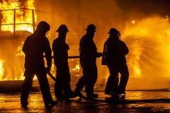 冲洗在火下的消防队员 库存照片