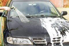冲洗车身用从水管的水 免版税库存照片