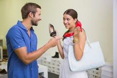 决定哪双鞋子的年轻夫妇选择 库存图片