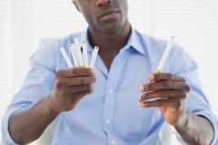 决定在电子或正常香烟之间的商人 免版税库存照片