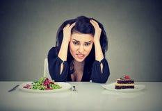 决定的妇女疲倦了于饮食制约吃她热衷的健康食物或蛋糕 库存图片