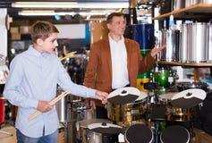 决定磁鼓单元的少年和父亲在音乐商店 免版税库存照片