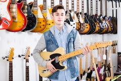 决定适当的amp的少年顾客在吉他商店 免版税图库摄影