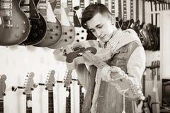 决定适当的amp的少年顾客在吉他商店 免版税库存照片