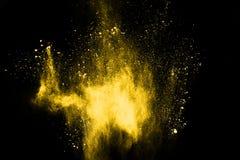 冷冻在黑背景隔绝的黄色尘末爆炸的行动 免版税库存照片