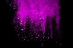 冷冻爆炸在黑背景的紫色粉末的行动 免版税库存照片