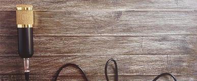 冷凝器金话筒和缆绳在一张木桌上 从右边的光 免版税库存照片
